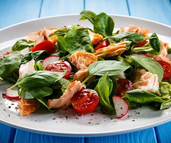 Salmon salad with green vegetables, tomatoes.